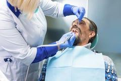Дантист с зубами инструмента очищая Стоковые Изображения