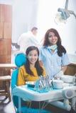 Дантист усмехаясь с женским пациентом в зубоврачебной клинике стоковая фотография rf