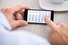 Дата календаря бизнесмена касающая на мобильном телефоне Стоковые Изображения