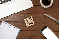 Дата календаря с кофейной чашкой и книгой мобильным телефоном на таблице Стоковые Фото