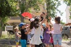 Дата: 17/5/2015 Положение: Парк в Афинах Волшебная выставка с Tristan Счастливые дети пробуя уловить confetti Стоковое Изображение