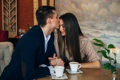 Датировать в кафе Красивые молодые пары сидя в кафе, выпивая влюбленность кофе, датируя Стоковые Фото