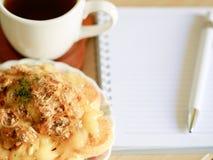 Датское печенье с чашкой горячего чая и тетрадью ручки и малых на деревянной таблице в утреннем времени Стоковое Изображение