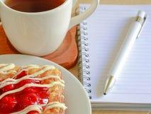 Датское печенье с чашкой горячего чая и тетрадью ручки и малых на деревянной таблице в утреннем времени и красным сердцем для вал Стоковые Фото