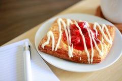 Датское печенье с чашкой горячего чая и тетрадью ручки и малых на деревянной таблице в утреннем времени Стоковая Фотография