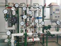 Датчики и приборы показывая параметры горячей воды в системе отопления большого дома Переплетение труб техническо стоковая фотография
