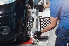 Датчик решетки устанавливает механика на автомобиле Стойка автомобиля с колесами датчиков для погиба выравнивания проверяет внутр стоковая фотография
