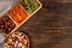 Даты, высушенные абрикосы и кивиы в Compartmental блюде и ассортименте гаек в деревянном шаре на темном деревянном столе стоковое фото