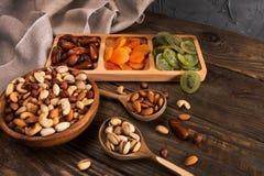 Даты, высушенные абрикосы и кивиы в Compartmental блюде и ассортименте гаек в деревянном шаре на темном деревянном столе стоковое изображение