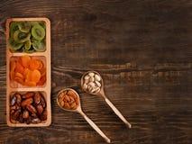 Даты, высушенные абрикосы и кивиы в Compartmental блюде и гайки в деревянной ложке на темном деревянном столе стоковая фотография rf