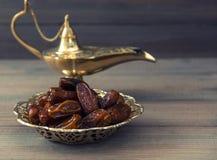 Даты и золотая аравийская лампа на деревянной предпосылке стоковые изображения