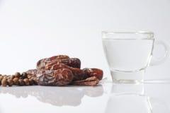 Даты и стекло воды - вещей используемых для того чтобы сломать быструю на заходе солнца во время мусульманского месяца Рамазана Стоковые Изображения RF