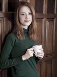 двери кофе выпивая девушку около древесины Стоковая Фотография
