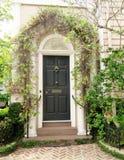 Двери при арка кирпича предусматриванная в зеленых лозах в Чарлстоне, Южной Каролине Стоковая Фотография