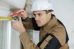 Дверная рама мужского построителя рабочий-строителя измеряя с рулеткой стоковое изображение
