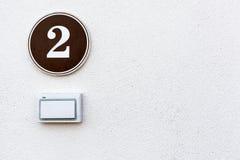 Дверной звонок и плита с номер два на стене, copyspace стоковая фотография