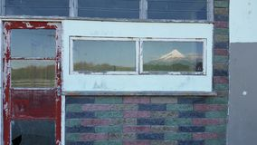 Дверь стены Bricked красная с Mt Taranaki отразила в окне Стоковая Фотография