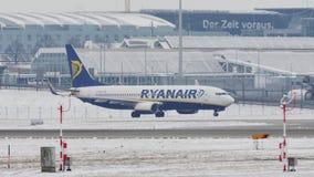 Двигатель Ryanair Боинга ездя на такси на снежном взлётно-посадочная дорожка, авиапорте Мюнхена