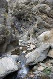 Двигатели воды пропускают вниз от валуна в горах Тянь-Шань Стоковое Изображение