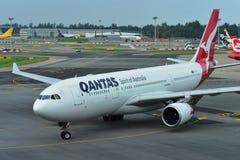 Двигатель аэробуса A330 Qantas widebody ездя на такси на авиапорте Changi Стоковые Фотографии RF