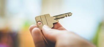 Двигать в новый дом: Закройте вверх руки держа ключ Свойство и недвижи стоковые изображения rf