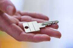Двигать в новый дом: Закройте вверх руки держа ключ Свойство и недвижимость стоковое фото rf