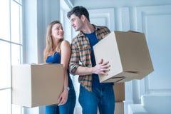 Двигать к новой жизни Девушка и парень держа коробки для двигать Стоковое фото RF