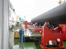Двигать трубопровод на роликах от палубы к мастерской собрания Работы на установке подводного газопровода Стоковое Изображение