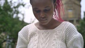 Двигая близкий отснятый видеоматериал молодой Афро-американской книги и усаживания чтения студента на стенде в парке около универ видеоматериал