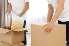 Двигая работники обслуживания с картонными коробками и пожитки в комнате стоковое фото rf