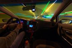 Движение автомобиля на ноче на взгляде скорости от внутренней, гениальной дороги с светами с автомобилем на высокой скорости Стоковое Изображение