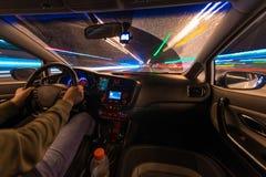 Движение автомобиля на ноче на взгляде скорости от внутренней, гениальной дороги с светами с автомобилем на высокой скорости Стоковые Изображения