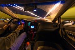 Движение автомобиля на ноче на взгляде скорости от внутренней, гениальной дороги с светами с автомобилем на высокой скорости Стоковые Фотографии RF
