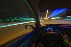 Движение автомобиля на ноче на шоссе страны на высокой скорости просмотра от внутренности с водителем Рука дальше Стоковая Фотография RF