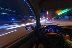 Движение автомобиля на ноче на шоссе страны на высокой скорости просмотра от внутренности с водителем Рука дальше Стоковая Фотография