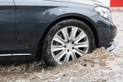 Движение автомобиля через большую лужицу воды брызгает от колес на дороге улицы Стоковые Изображения