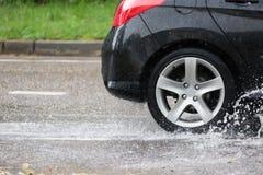 Движение автомобиля через большую лужицу воды брызгает от колес на дороге улицы Стоковое Изображение