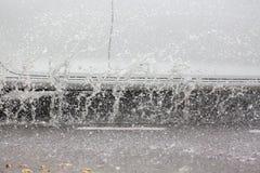 Движение автомобиля через большую лужицу воды брызгает от колес на дороге улицы Стоковая Фотография RF