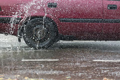 Движение автомобиля через большую лужицу воды брызгает от колес на дороге улицы Стоковые Изображения RF