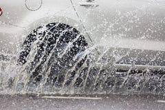 Движение автомобиля через большую лужицу воды брызгает от колес на дороге улицы Стоковые Фото