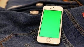 Движение джинсов дисплея и зеленого телефона экрана