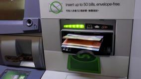 Движение женщины разделяя деньги на машине ATM