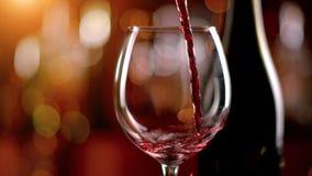 Движение замораживания лить красное вино в кубок стоковое фото rf