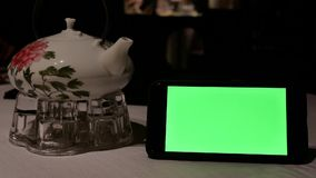 Движение зеленого телефона экрана при люди нерезкости есть еду внутри ресторана сток-видео
