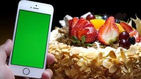 Движение именниного пирога и руки плодоовощ держа зеленый телефон экрана акции видеоматериалы