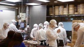 Движение людей замешивает тесто и формирует его с их руками для того чтобы сделать вареники