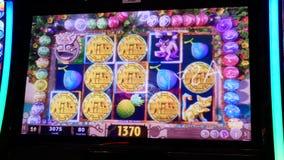 Движение людей играя торговый автомат и выигрывая большой приз внутри казино