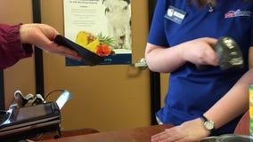 Движение людей используя талон на телефоне и клерка просматривая его на кассе сток-видео