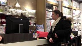 Движение людей оплачивая кредитную карточку для того чтобы купить подушку на магазине тюфяка