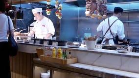 Движение людей принимая еду и шеф-повара варя зажаренную еду видеоматериал